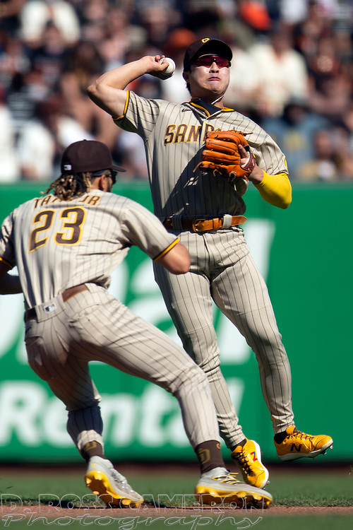 San Diego Padres second baseman Ha-Seong Kim (7) leaves his feet but cannot throw out San Francisco Giants' Darin Ruf at first during the fourth inning of a baseball game, Saturday, Oct. 2, 2021, in San Francisco. Padres shortstop Fernando Tatis Jr. (23) watches the play. (AP Photo/D. Ross Cameron)