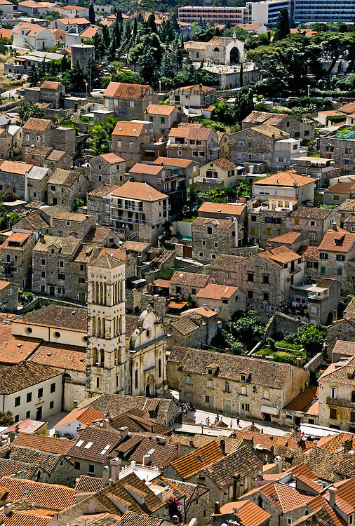 Old and new ; old village structures with modern hotel visible beyond.  View of Hvar rooftops, including church bell tower and houses with rooftop solar panels.