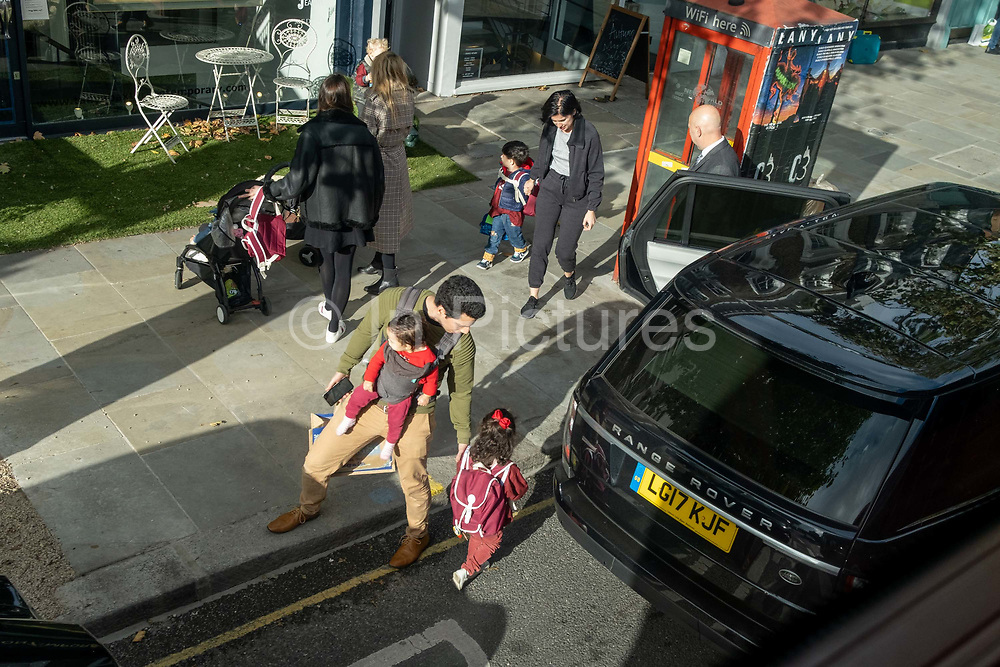 Primary schoolchildren and parents at the end of the day in West London, during the second wave of the Coronavirus pandemic, and when the capital is designated by the government as a Tier 2 restriction, on 20th October 2020, in London, England.