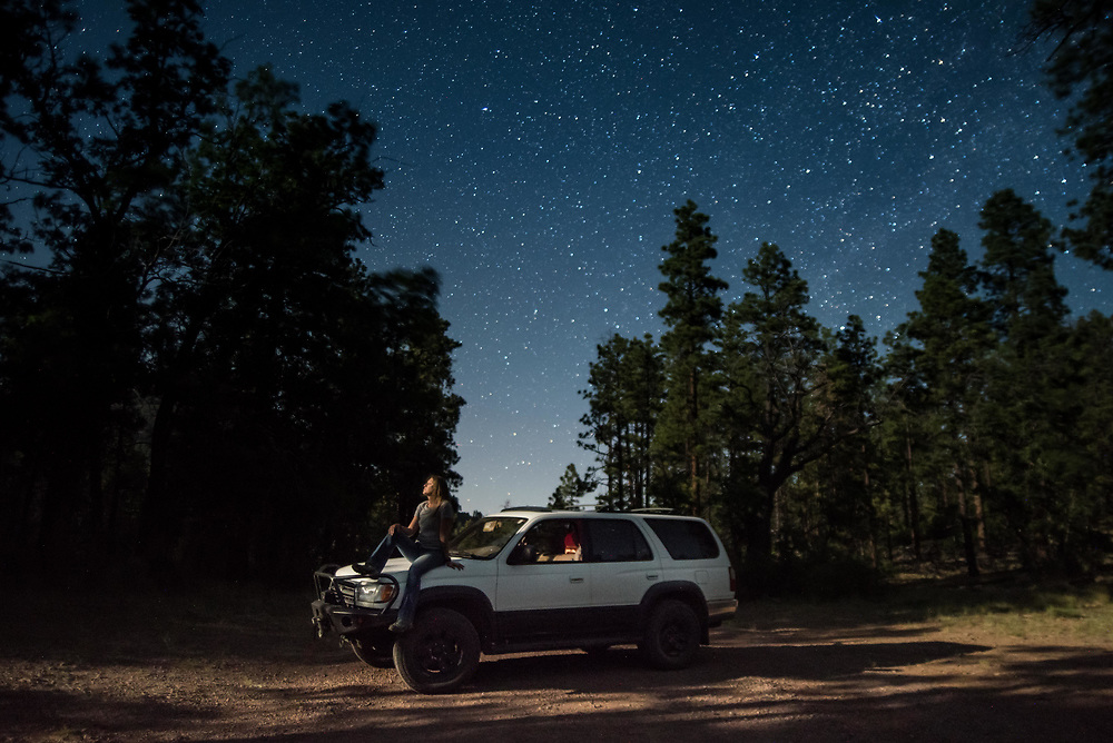 A woman sits on her 98' Toyota 4Runner under the stars in Arizona