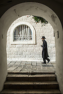 """An Haredi Jew walks in Jerusalem Jewish Quarter in the Old City. The Jewish Quarter is one of the four traditional quarters of the Old City ofJerusalem and the only recently rebuilt after a history of destruction.<br /> While most residents of Jerusalem in the centuries preferred to live near members of their own community, there were Muslims living in the Jewish Quarter and Jews living in the Muslim Quarter. Many Jews moved to the Muslim Quarter toward the end of the 19th century due to intense overcrowding in the Jewish Quarter.<br /> In 1948 during the Arab-Israeli War, its population of about 2,000 Jews was besieged, and forced to leave en masse. A Jordanian commander is reported to have told: """"For the first time in 1,000 years not a single Jew remains in the Jewish Quarter. Not a single building remains intact. This makes the Jews' return here impossible.""""<br /> The Jewish Quarter remained under Jordanian occupation until the Six-Day War in June 1967 when Israel occupied it. During the first week after taking the Old City, the Moroccan Quarter was razed to create a plaza at the foot of the Western Wall.<br /> In April 1968, the government expropriated 129 dunams (about 32 acres) of land which had made up the Quarter before 1948. In 1969, the Jewish Quarter Development Company was established under the auspices of the Construction and Housing Ministry to rebuild the desolate Jewish Quarter."""