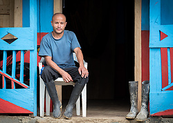 16 November 2018, San José de León, Mutatá, Antioquia, Colombia: 30-year-old Jorge rests on the porch of his house. Following the 2016 peace treaty between FARC and the Colombian government, a group of ex-combatant families have purchased and now cultivate 36 hectares of land in the territory of San José de León, municipality of Mutatá in Antioquia, Colombia. A group of 27 families first purchased the lot of land in San José de León, moving in from nearby Córdoba to settle alongside the 50-or-so families of farmers already living in the area. Today, 50 ex-combatant families live in the emerging community, which hosts a small restaurant, various committees for community organization and development, and which cultivates the land through agriculture, poultry and fish farming. Though the community has come a long way, many challenges remain on the way towards peace and reconciliation. The two-year-old community, which does not yet have a name of its own, is located in the territory of San José de León in Urabá, northwest Colombia, a strategically important corridor for trade into Central America, with resulting drug trafficking and arms trade still keeping armed groups active in the area. Many ex-combatants face trauma and insecurity, and a lack of fulfilment by the Colombian government in transition of land ownership to FARC members makes the situation delicate. Through the project De la Guerra a la Paz ('From War to Peace'), the Evangelical Lutheran Church of Colombia accompanies three communities in the Antioquia region, offering support both to ex-combatants and to the communities they now live alongside, as they reintegrate into society. Supporting a total of more than 300 families, the project seeks to alleviate the risk of re-victimization, or relapse into violent conflict.