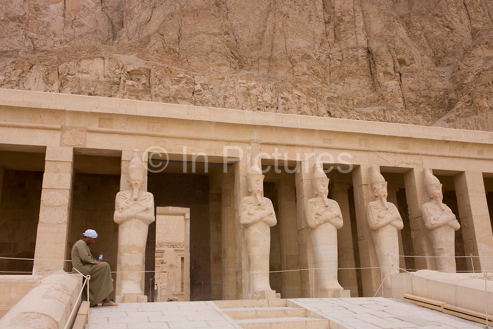 """Portrait of a local guide near the colossi of Pharaohs at the otherwise deserted ancient Egyptian Temple of Hatshepsut near the Valley of the Kings, Luxor, Nile Valley, Egypt. According to the country's Ministry of Tourism, European visitors to Egypt is down by up to 80% in 2016 from the suspension of flights after the downing of the Russian airliner in Oct 2015. Euro-tourism accounts for 27% of the total flow and in total, tourism accounts for 11.3% of Egypt's GDP. The Mortuary Temple of Queen Hatshepsut, the Djeser-Djeseru, is located beneath cliffs at Deir el Bahari (""""the Northern Monastery""""). The mortuary temple is dedicated to the sun god Amon-Ra and is considered one of the """"incomparable monuments of ancient Egypt."""" The temple was the site of the massacre of 62 people, mostly tourists, by Islamists on 17 November 1997."""