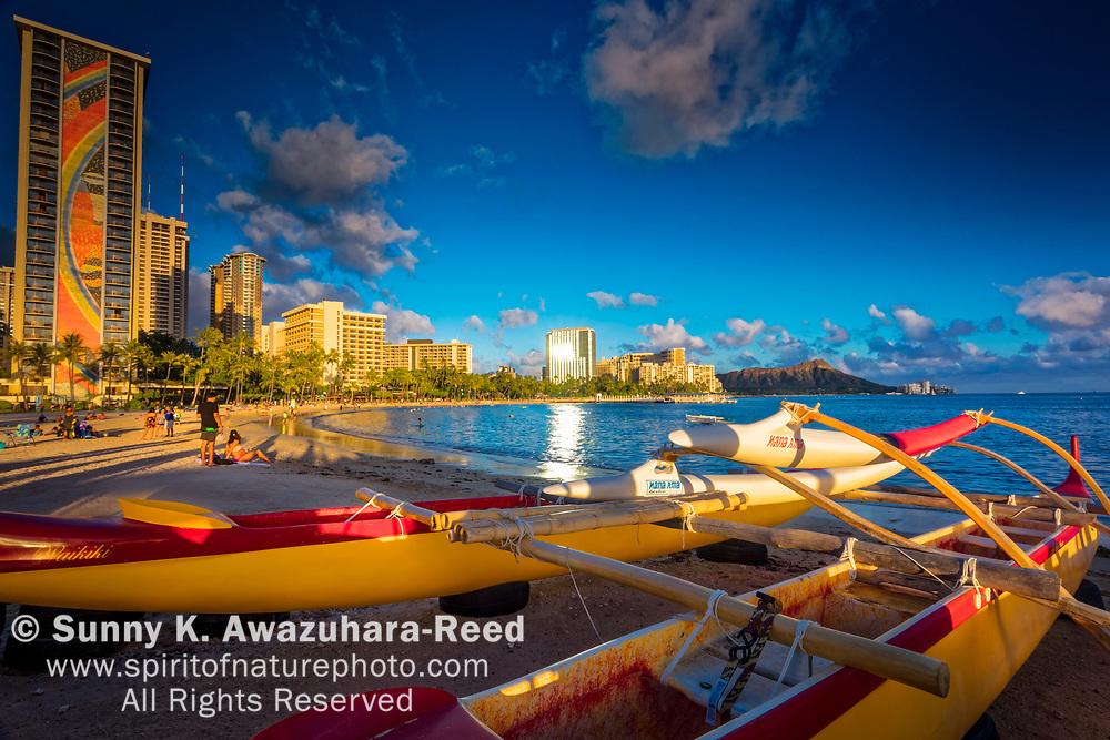Outrigger canoe on Kahanamoku Beach. Highrise Resorts and Diamond Head in the background. Honolulu, Oahu, Hawaii.