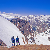 Hikers overlook road-served ski slopes near Beartooth Pass, in Beartooth Mountains, near Yellowstone in Wyoming.