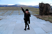 Young woman posing Buzludzha monument former communist party headquarters, Bulgaria, eastern Europe