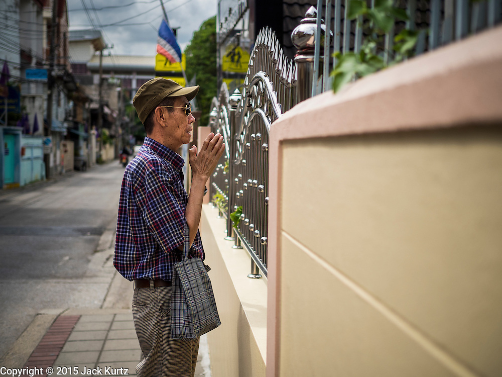 22 JULY 2015 - BANGKOK, THAILAND:     A man prays in front of Christ Cemetery, a Roman Catholic Cemetery in Bangkok. It's in the middle of a neighborhood of Catholic Churches and schools between Samsen Road and the Chao Phraya River in the Dusit section of Bangkok.           PHOTO BY JACK KURTZ
