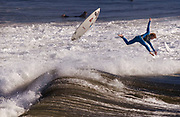 A surfer wipes out as he braves the high surf at Huntington Beach, CA.