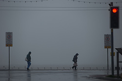 © Licensed to London News Pictures . 17/06/2015. Blackpool  , UK . People walking along Blackpool Promenade  as fog obscures the view of the sea . Rain and fog over Blackpool today ( Wednesday 17th June 2015 ) . Photo credit : Joel Goodman/LNP