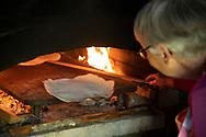 A woman baking flatbread at the Hardanger Folk Museum in Utne, Vestlandet, Norway