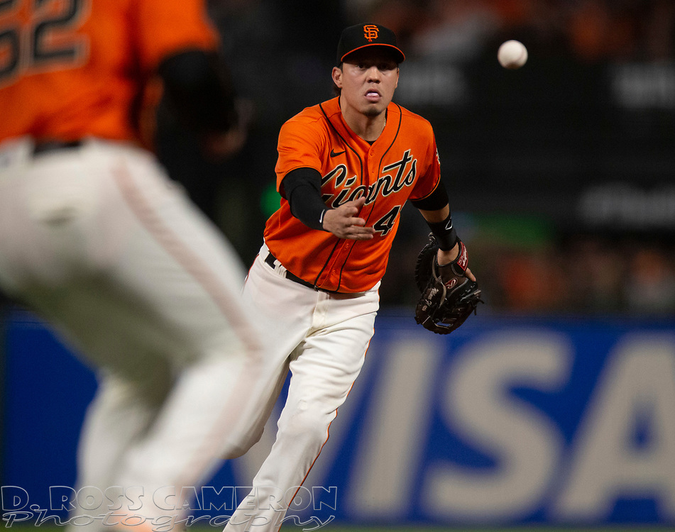 Oct 1, 2021; San Francisco, California, USA; San Francisco Giants first baseman Wilmer Flores (41) flips the ball to pitcher Dominic Leone (52) covering first in time to retire San Diego Padres catcher Victor Caratini during the seventh inning at Oracle Park. Mandatory Credit: D. Ross Cameron-USA TODAY Sports