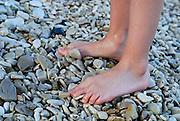 Young girl's feet on shingle beach, Racisce, island of Korcula, Croatia