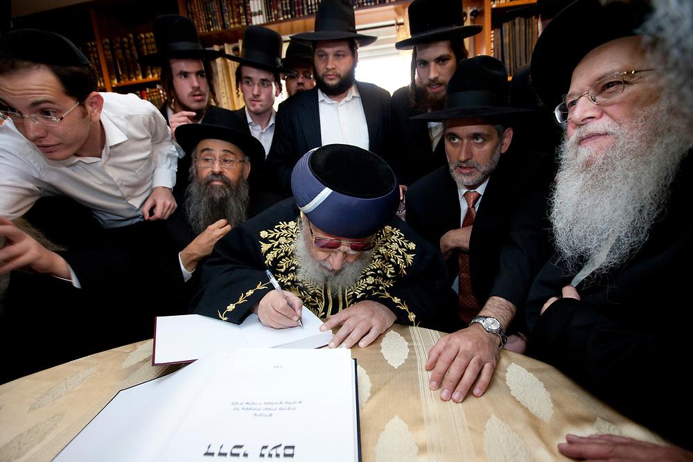 Spiritual leader of the Ultra-Orthodox Shas party, Rabbi Ovadia Yosef (sitting c), dedicates a book to Slonim Grand Rabbi Shmuel Berezovsky (sitting R) during their meeting in Jerusalem, on June 27, 2010.