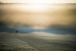 © Licensed to London News Pictures. 04/11/2020. London, UK. Two people walk through a frost and mist covered landscape at sunrise in Richmond Park, south west London on a cold Autumn morning. Photo credit: Ben Cawthra/LNP