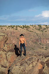 shirtless muscular cowboy on a rock formation
