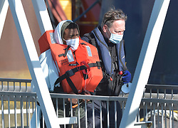 © Licensed to London News Pictures. 2/08/2021. Dover, UK. A  migrant is helped ashore by a Border Force officer at Dover Harbour in Kent after crossing the English Channel. Hundreds of migrants have made the crossing in recent weeks. Photo credit: Stuart Brock/LNP