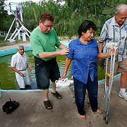 Teresa Flores, of Corpus Christi, walks away from the charquito, or small pond, while Daniel Hinojosa, second from left, and her husband Rudy Flores look on after a spiritual healing session with Alberto Salinas, left, at his home and shrine to the Mexican folk saint Nino Fidencio in Edinburg. Flores, who normally walks with crutches due to hip problems, said she felt strong and that she no longer needed the crutches after the being healing session.<br /> Nathan Lambrecht/The Monitor