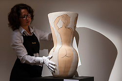 """© Licensed to London News Pictures. 18/11/2016. London, UK. A staff member examines """"Grande Vase Aux Femmes Nues"""" by Pablo Picasso (est. GBP250-350k), at the preview at Sotheby's of works on view at four upcoming November auctions featuring Modern & Post-War British Art, A Painter's Paradise (Julian Trevelyan & Mary Fedden at Durham Wharf), Scottish Art and Picasso Ceramics from the Lord & Lady Attenborough Private Collection. Photo credit : Stephen Chung/LNP"""