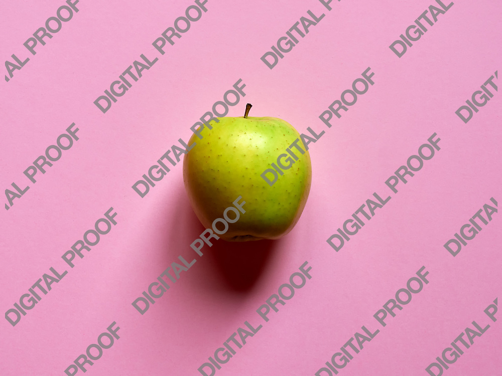 Above view of a Green apple isolated in a pink background in studio