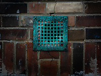 A turquoise metal grate over an exerior vent out of a brick house.