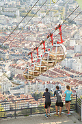 Teenagers looking over Grenoble-Bastille cable car and rooftops of Grenoble, France