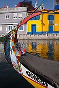 Typical landscape on the Canal de S. Roque with the bow of a traditional Moliceiro boat and the background of brightly painted traditional homes, on 18th July, at Aveira, Portugal. The Moliceiro is the name given to Portuguese boats which use Ria de Aveiro lagoon area of Rio Vouga. They were originally used for the harvesting of seaweed but are nowadays used for tourism.