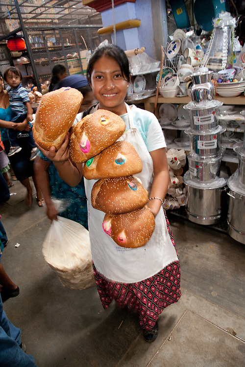 "North America, Mexico, Oaxaca Province, Ocotlan, teenage girl with special bread (""'pan de muertos"")  for sale during annual Day of the Dead (Dias de los Muertos) celebration in November"