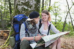 Young couple studying a map in forest, Bavaria, Germany