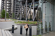 A man carries a box outside the Aviva Insurance building on Leadenhall Street, on 30th May 2018, in London, England.