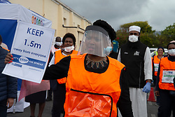 """Parkwood, Cape Town, South Africa: Nomafrench Mbombo, Western Cape Health Minister, holds up a sign that says """"Keep 1.5m away from everyone,"""" as she speaks to community health workers in Parkwood, Capetown, on Thursday, April 16, 2020, as they are doing door-to-door COVID-19 screenings here. The Western Cape government is ramping up mass screening and testing to stop the spread in vulnerable communities, such as low-income areas where many are living in multi-family households in crowded spaces. The aim is early detection, so that those who are testing positive can be removed to quarantine elsewhere. PHOTO: EVA-LOTTA JANSSON"""