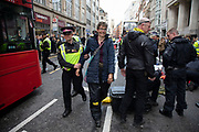 Climate change activists from the Extinction Rebellion group are arrested after being locked on and glued together outside Goldman Sachs International on Fleet Street in the heart of the City of London financial district in protest that the government is not doing enough to avoid catastrophic climate change and to demand the government take radical action to save the planet, on 25th April 2019 in London, England, United Kingdom. Extinction Rebellion is a climate change group started in 2018 and has gained a huge following of people committed to peaceful protests.