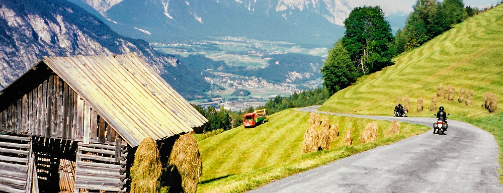 Two riders enjoy the view from a typical road in the Bavarian Alps of Germany.