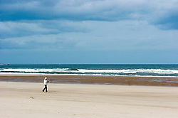 A lone female walks on an almost deserted Beach close to Arbroath Scotland..Copyright Paul David Drabble.27 May 2007