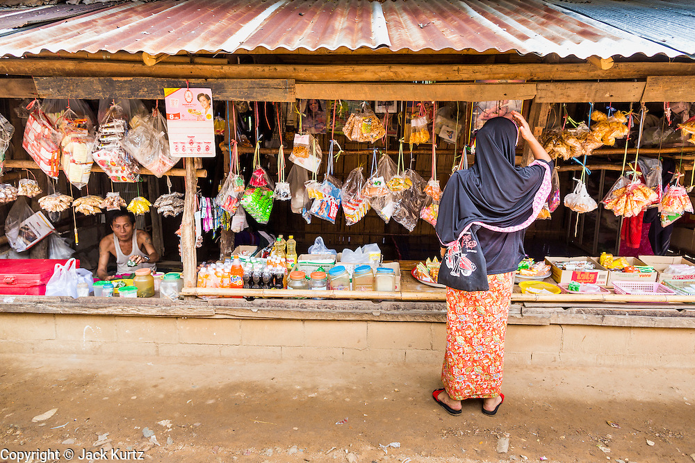 22 MAY 2013 - MAELA REFUGEE CAMP, TAK, THAILAND:  A Burmese Muslim woman shops at a snack stand in Mae La Refugee Camp. Mae La (Maela) is the largest refugee camp for Burmese in Thailand. Over 90% are ethnic Karen. It was established in 1984 in Tha Song Yang District, Tak Province in the Dawna Range area and currently houses 40,000 refugees. The Thai government has indicated that it would like to close the camp and repatriate the refugees to Myanmar as soon as the political situation in Myanmar is stable enough.   PHOTO BY JACK KURTZ