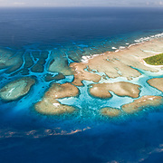 This is an aerial panorama of Maninita Island in the Vava'u island group of the Kingdom of Tonga. The island sits atop an extensive coral reef structure, which is for the most part not visible from the surface of the ocean. The reefs extend into the background, reaching the smaller island of Fonuafo'ou. This photograph was taken a few days before the full moon. The pinkish-red threads visible on the ocean surface are billions of gametes, perhaps spawned from the coral around Maninita and other nearby reefs.
