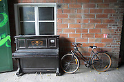"""Discarded piano and bicycle.<br /><br />The Freegan Pony is an alternative restaurant housed in a squat. It was founded in 2015 by Aladdin Charni with three other collaborators. The restaurant specialises in cheap vegetarian cuisine, serving meals which guests reserve a place through a Facebook group, paying €2 a meal. The restaurant meals contain unsold and donated food, collected from wholesellers at the Paris Rungis vegetable market. The Freegan Pony is located at the Porte de la Vilette on the outskirts of Paris, at the entrance to the peripherique outer circle motorway.<br /><br />Freegans are people who employ alternative strategies for living based on limited participation in the conventional economy and minimal consumption of resources. Freeganism is the practice of reclaiming and eating food that has been discarded. People who attempt to live an ethical lifestyle by reusing trash and rubbish thrown away by others.<br /><br />Freeganism is an ill-defined activity and is a subset of the larger anti-capitalist and environmental protest movements. It embraces alternative, anti-consumerist lifestyles. Freegan practices also include co-operative living, squatting and """"freecyling"""", or matching things that people want to get rid of with things other people need"""