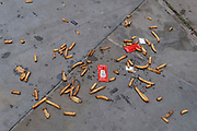 Along with sachets of salt and tomato ketchup, the remains of a portion of chips aka French Fries lie scattered on the pavement on Londons Southbank, on 10th June 2021, in London, England.