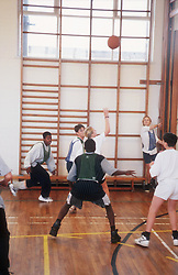 Secondary school pupils playing game of netball during indoor PE lesson,