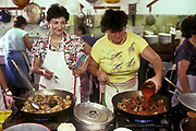 A women smiles as she and a colleague prepare a lunch of Chicken and beef casserole in a vilage outside Florence, Italy