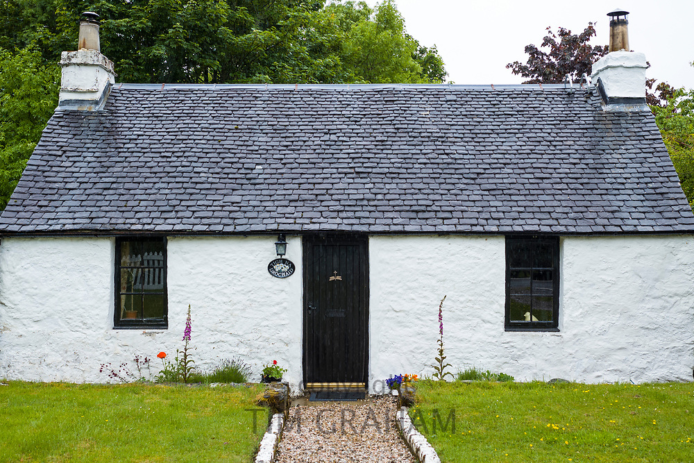 Quaint traditional whitewashed cottage with black front door and tiled roof in Port Appin, Argyll and Bute, Scotland