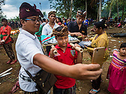 13 JULY 2016 - UBUD, BALI, INDONESIA:  A father takes a selfie of his son during the mass cremation in Ubud Wednesday. Local people in Ubud exhumed the remains of family members and burned their remains in a mass cremation ceremony Wednesday. Almost 100 people will be cremated and laid to rest in the largest mass cremation in Bali in years this week. Most of the people on Bali are Hindus. Traditional cremations in Bali are very expensive, so communities usually hold one mass cremation approximately every five years. The cremation in Ubud will conclude Saturday, with a large community ceremony.     PHOTO BY JACK KURTZ