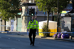 © Licensed to London News Pictures. 22/09/2021. London, UK. Police officer guards the crime scene on Green Lanes, Haringey in north London following a fatal shooting. Police were called just after 10.30 pm on Tuesday 21, September to reports of a man shot on Green Lanes, close to Turnpike Lane underground station. Officers including firearm officers, attended with the London Ambulance Service and the London Air Ambulance. Despite their efforts, a man in his early 20s was pronounced dead at the scene at 10.56pm. Photo credit: Dinendra Haria/LNP