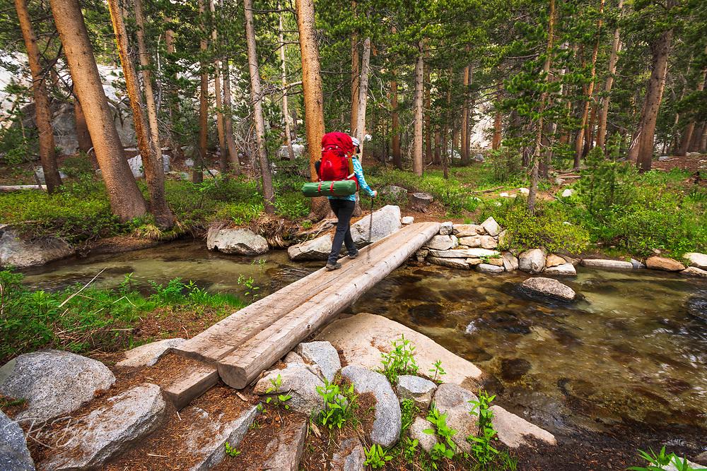 Backpacker crossing creek in the John Muir Wilderness, Sierra Nevada Mountains, California USA