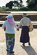 Japanese tourist couple at Dharmarajika Stupa at Sarnath ruins near Varanasi, Benares, Northern India