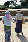 Japanese tourist couple at Dharmarajika Stupa at Sarnath ruins near Varanasi, Benares, Northern India