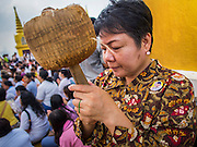 30 OCTOBER 2014 - BANGKOK, THAILAND: People pray at the base of the chedi during the parade marking the start of the annual temple fair at Wat Saket. Wat Saket is on a man-made hill in the historic section of Bangkok. The temple has golden spire that is 260 feet high which was the highest point in Bangkok for more than 100 years. The temple construction began in the 1800s in the reign of King Rama III and was completed in the reign of King Rama IV. The annual temple fair is held on the 12th lunar month, for nine days around the November full moon. During the fair a red cloth (reminiscent of a monk's robe) is placed around the Golden Mount while the temple grounds hosts Thai traditional theatre, food stalls and traditional shows.   PHOTO BY JACK KURTZ
