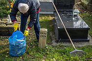 A woman rakes leaves together and puts them in a plastic bag at Rakowicki cemetery in Krakow, Poland 2019.
