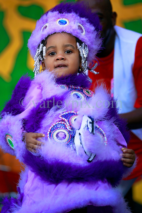 05 May 2013. New Orleans, Louisiana,  USA. .New Orleans Jazz and Heritage Festival. JazzFest..A young Mardi Gras indian takes to the stage with New Birth Brass Band. .Photo; Charlie Varley.