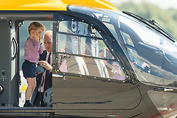 Prince George stands in a rescue helicopter as his father the Duke of Cambridge adjusts a helmet for him to wear, during a visit to Airbus in Hamburg, Germany with the Duchess of Cambridge and sister Princess Charlotte.