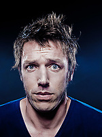 studio portrait on black background of a funny expressive caucasian man puckering anxious